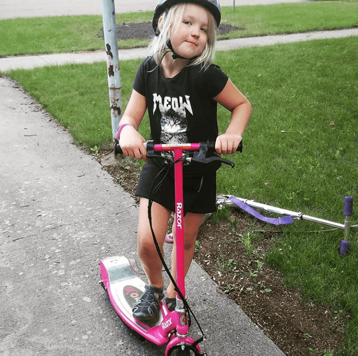 A little girl is enjoying riding razor e100 electric scooter