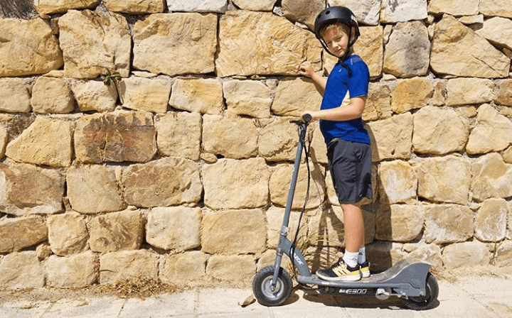 A boy is posing on Razor e300 electric scooter