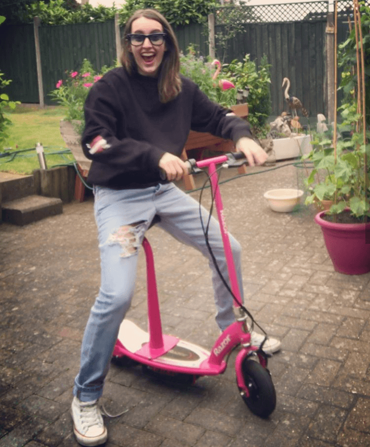 A happy girl on Razor e100 electric scooter with seat