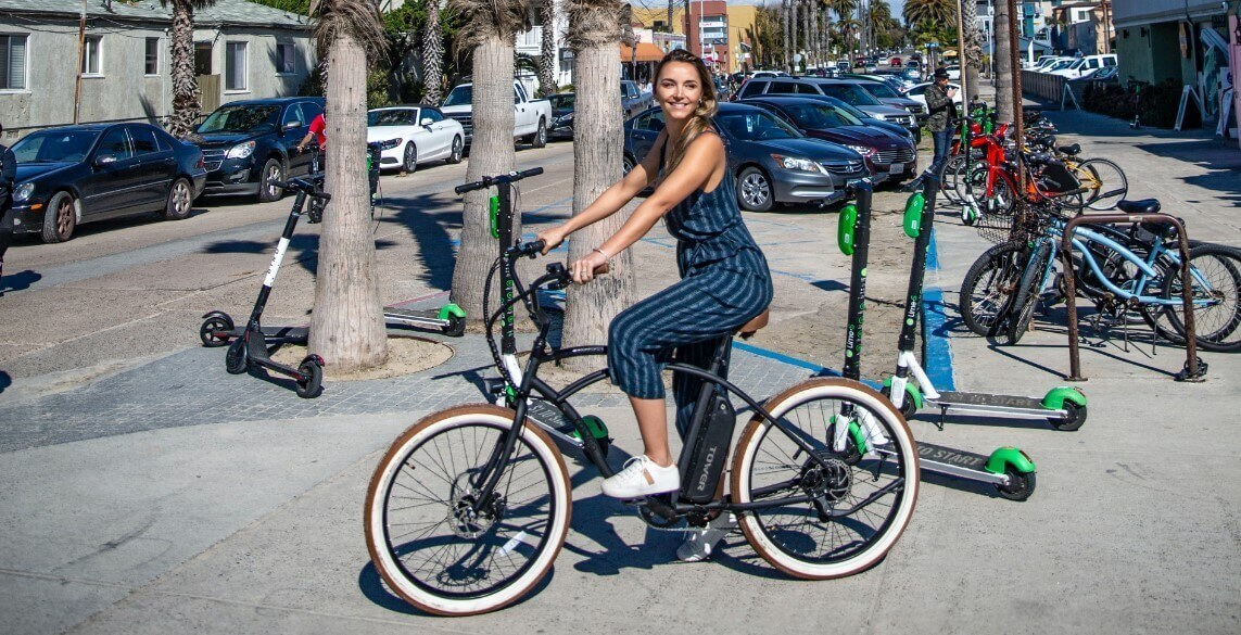 A woman is sitting on electric bicycle
