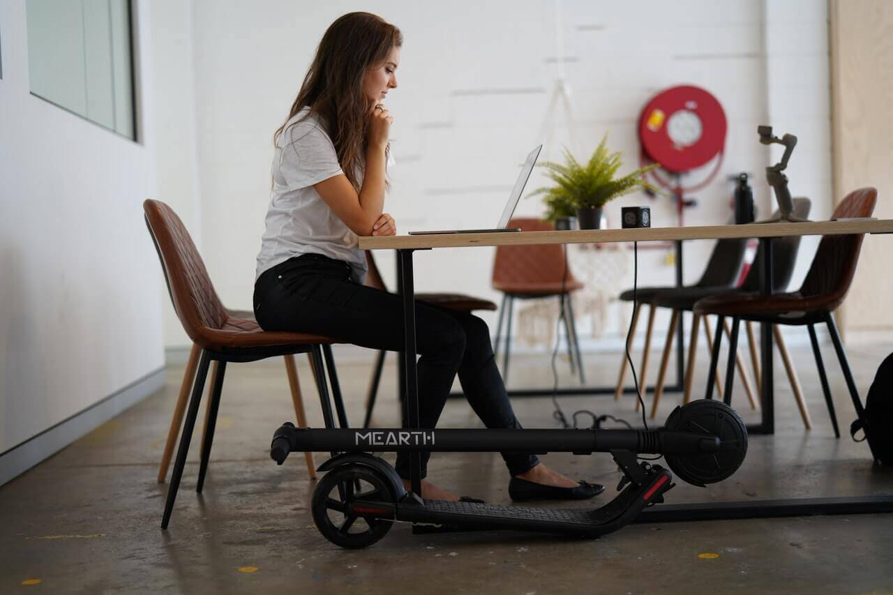A girl is working while foldable electric scooter is parked below desk.
