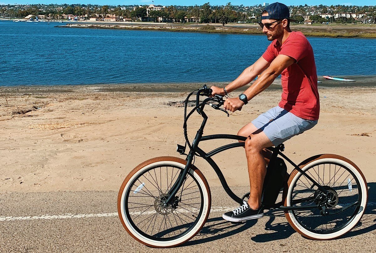 A man is riding electric bike on the road near the beach