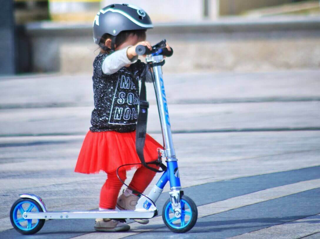 A little girl riding kick scooter