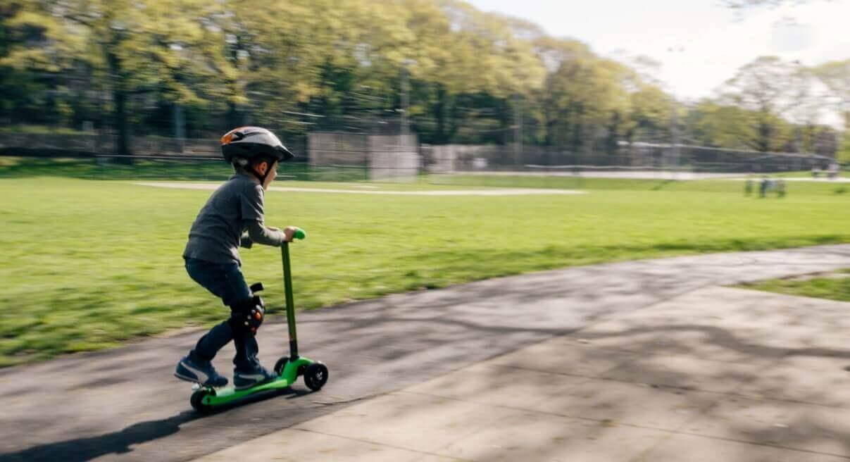 A child riding three wheel kick scooter