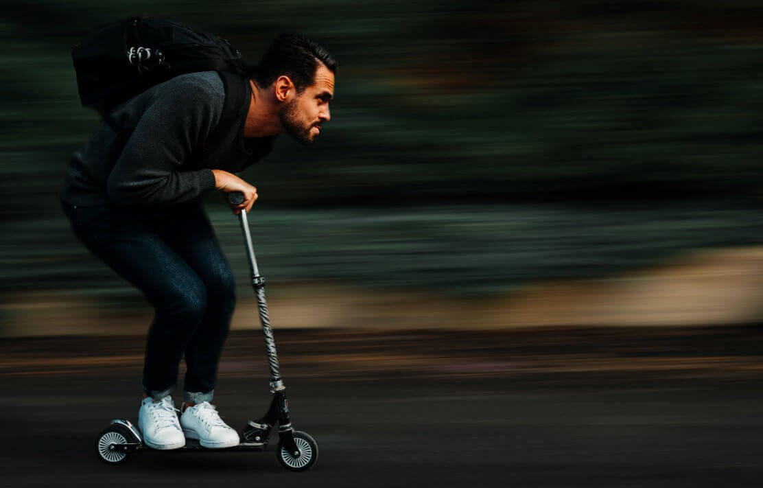 A man is speeding on small kick scooter