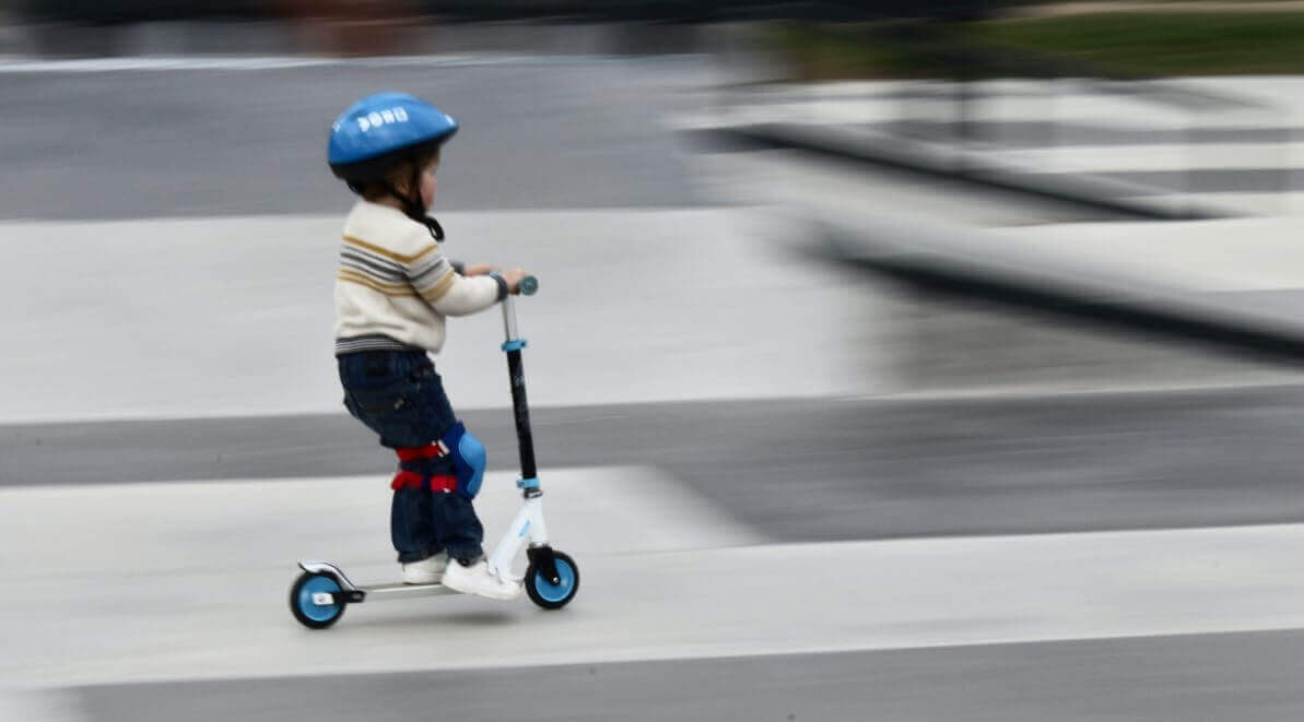 A child is having fun on kick scooter