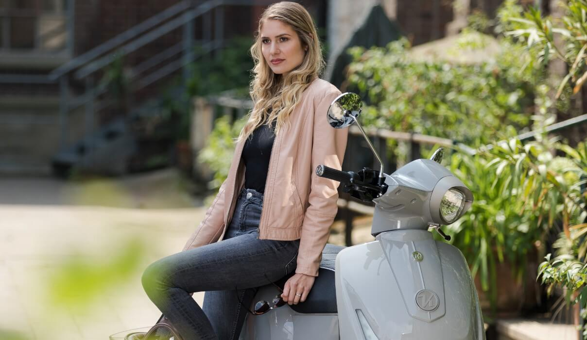 A girl is sitting on electric moped